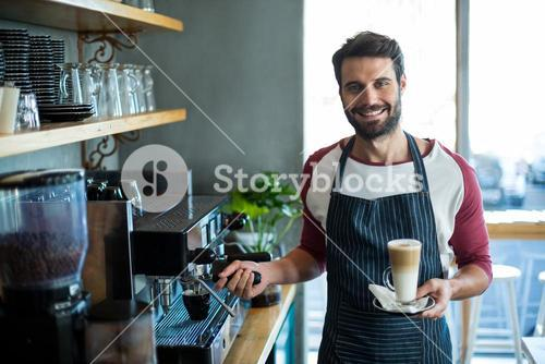 Smiling waiter holding cup of cold coffee at counter in cafe