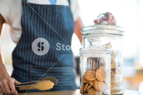 Waitress holding jar and tong in café