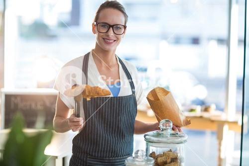 Smiling waitress packing croissants in paper bag at café