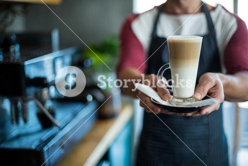 Waiter holding cup of cold coffee at counter in cafe