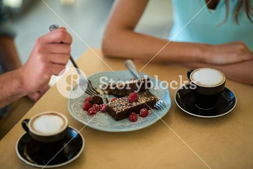 Couple eating pastry in café