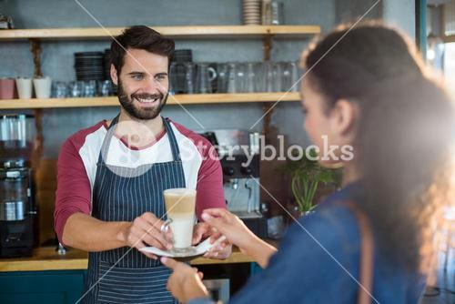 Waiter serving a cup of cold coffee to customer at counter