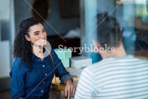 Smiling young couple interacting in café