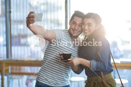 Young couple taking selfie in café