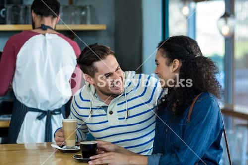 Smiling young couple having coffee in cafe