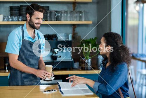 Waiter serving a cup of cold coffee to customer at table