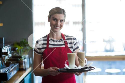 Smiling waitress holding cup of cold coffee at counter in cafe