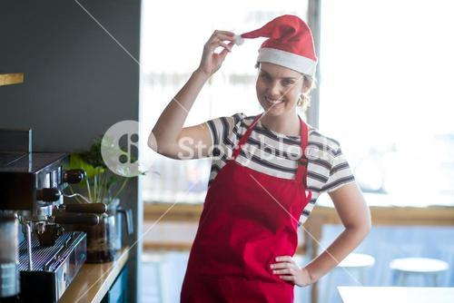 Portrait of waitress in santa hat standing with hand on hip