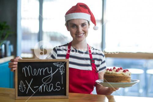 Portrait of waitress holding slate with merry x-mas sign and cake in café