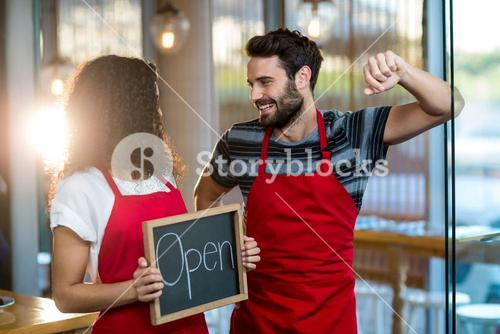 Waitress and waiter standing with open sign board in cafe
