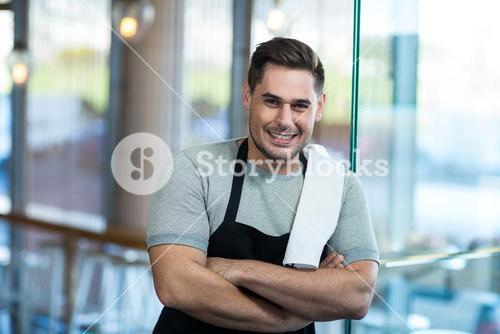 Smiling waiter leaning on glass door in café