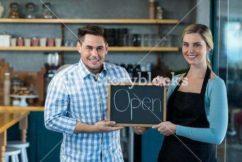 Waitress and man standing with open sign on slate in cafe