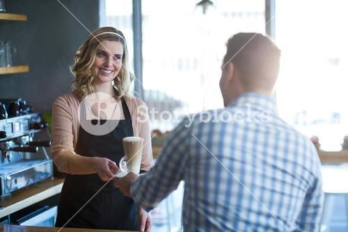 Waitress serving a cup of cold coffee to customer