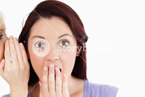 Close up of a shocked women being told a secret