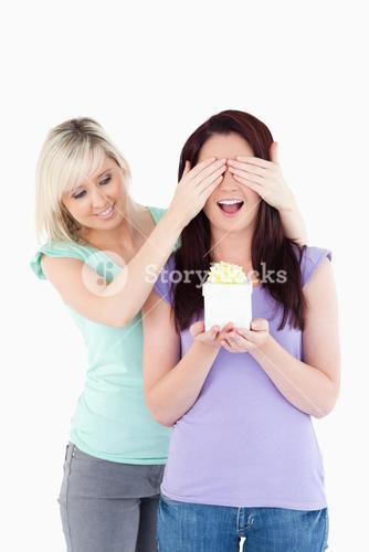 Young woman giving a gift to her friend