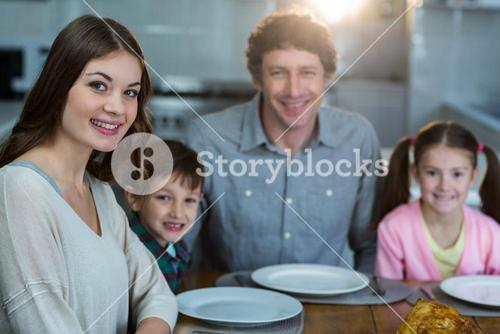 Portrait of happy family sitting on a dinning table