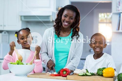 Portrait of mother with their children preparing food