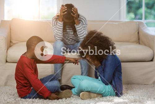 Children playing while mother sitting depressed