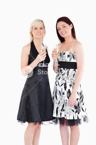 Smiling women in beautiful dresses with champaign