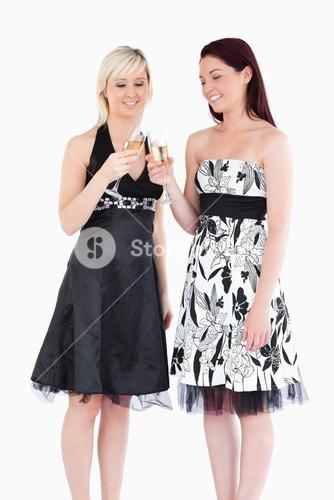 Smiling women in beautiful dresses toasting with champaign