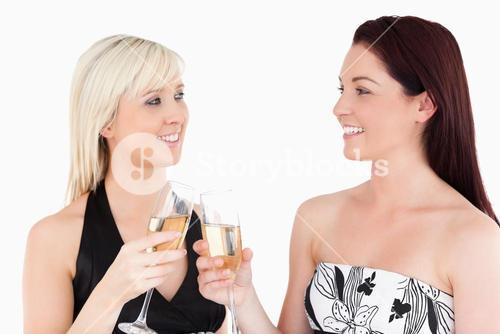 Gorgeous women in beautiful dresses toasting with champaign