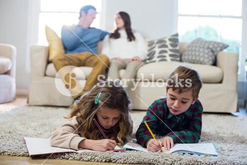 Children doing homework with parents in background