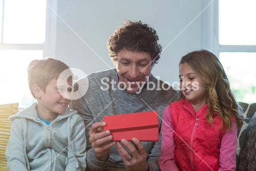 Father opening gift box with children