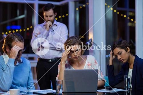 Tensed businesspeople working on laptop