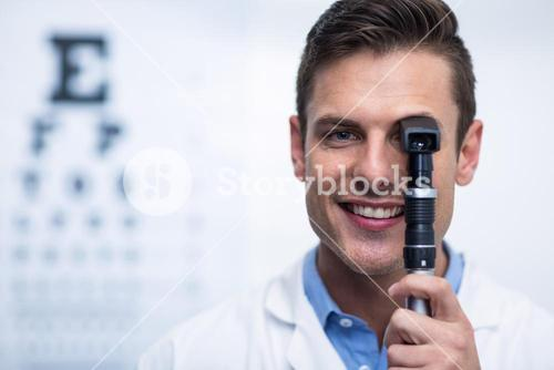 Smiling optometrist looking through ophthalmoscope