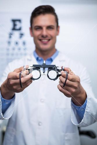 Smiling optometrist holding messbrille