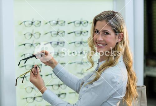 Smiling female customer selecting spectacles