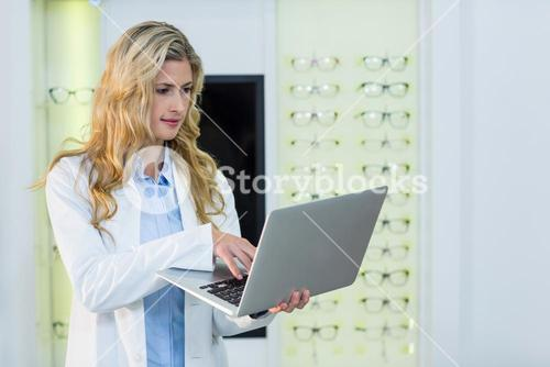 Optometrist using laptop in ophthalmology clinic