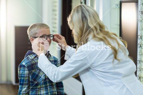 Female optometrist prescribing spectacles to young patient