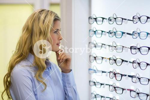 Thoughtful female customer selecting spectacles