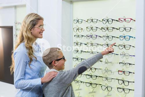 Mother and son selecting spectacles from display