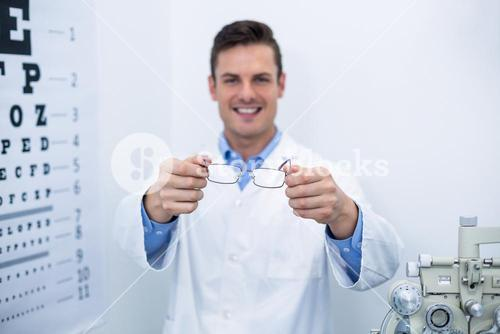 Smiling optometrist holding spectacles