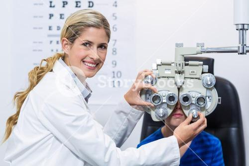 Female optometrist examining young patient on phoropter