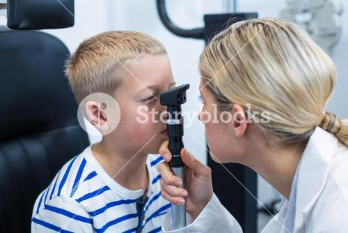 Female optometrist examining young patient with ophthalmoscope