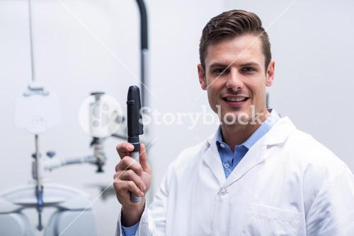 Smiling optometrist holding ophthalmoscope