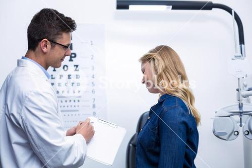 Optometrist discussing eye test report with female patient