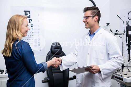 Optometrist shaking hands with female patient