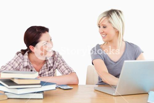 Women learning with laptop and books