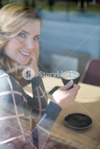 Woman having coffee in cafeteria
