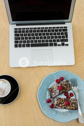 Delicious cakes, cup of coffee and laptop on table