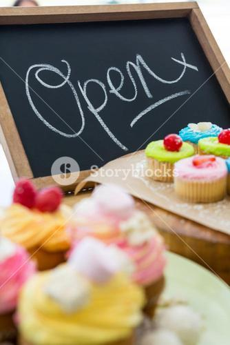 Close-up of various cupcakes on table with open signboard