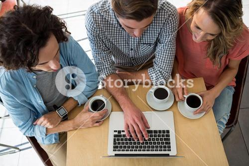 Three friends with coffee cups using a laptop