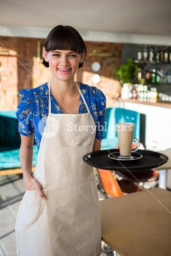 Smiling waitress holding a glass of coffee