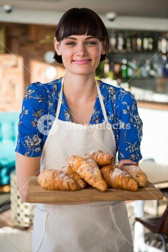 Smiling waitress holding a tray of croissants