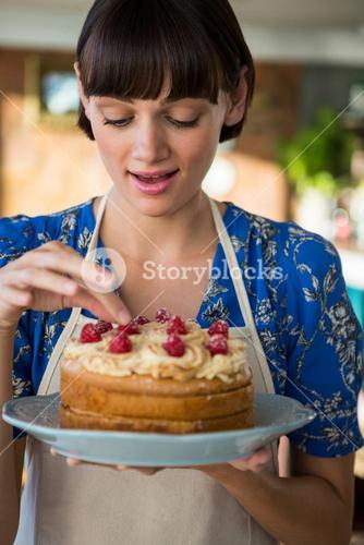 Waitress touching the cherry on the cake top