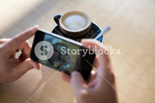 Female hands photographing a coffee cup
